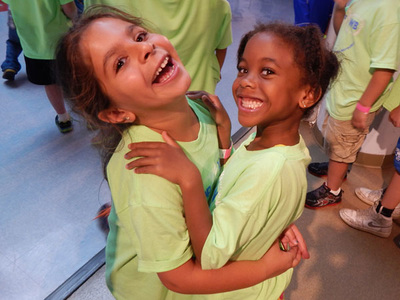 Two girls hug and smile up at the camera