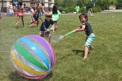 Two young boys spray water guns at a large rainbow-color ball