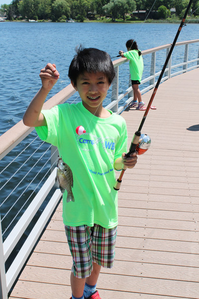 A young boy wearing a bright green Camp WB shirt holding a fishing pole and a small fish on the fishing pier at Marshbank Park