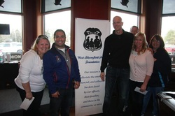 Two men and three women standing in front of the West Bloomfield Police Foundation banner