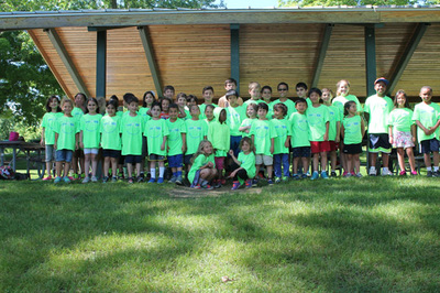 Camp WB campers wearing bright green shirts and standing in a line for a photograph outside on grass and by a wooden building