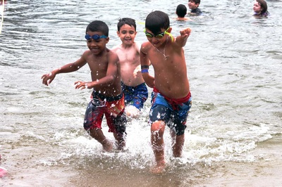 Three young boys racing out of a lake, one in the middle and two on either sides