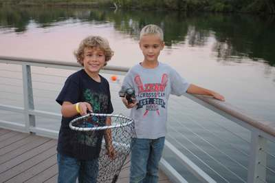 Two young boys holding a net by Cass Lake at Marshbank Park