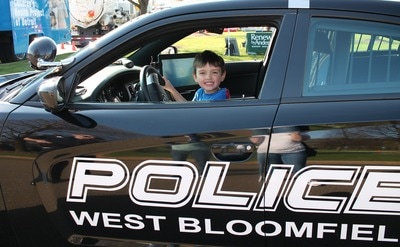 A boy sitting in the driver's seat of a West Bloomfield Police car