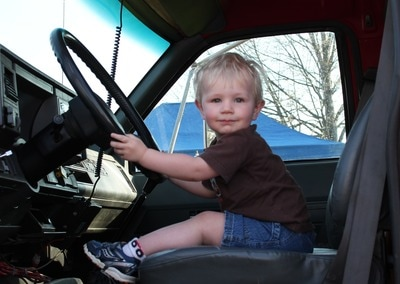 A toddler sitting in the seat of a big rig during Touch-a-Truck