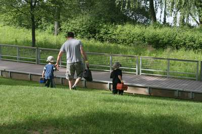 A dad and his two children walking towards the fishing pier at Marshbank Park