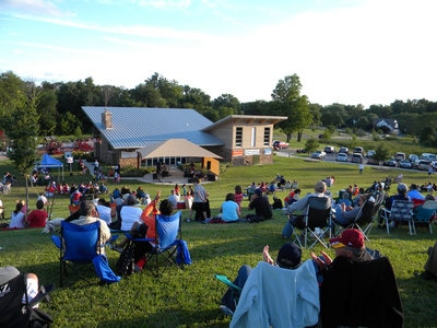 Families sitting on the concert hill at Marshbank Park during an annual concert